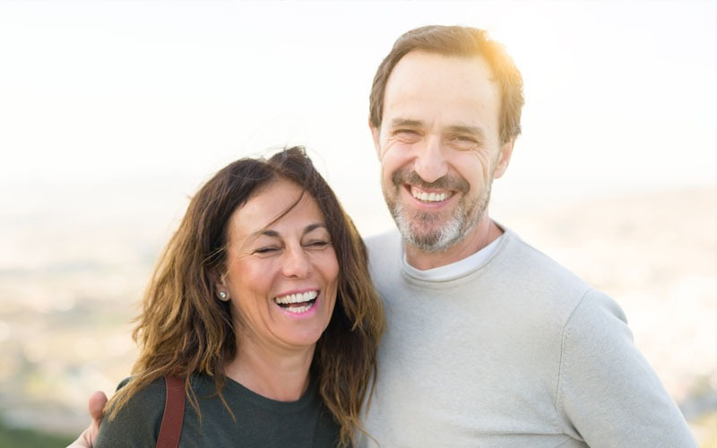 Smiling couple with dental implants