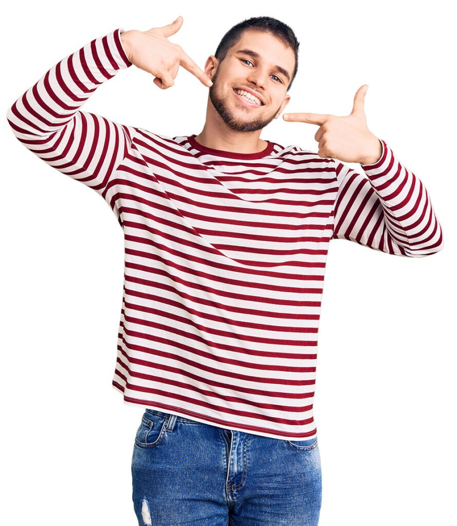 Man pointing at his white teeth